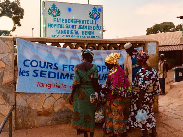 L'icona del gruppo WhatsApp Sediment Urinarie Afrique che mostra donne davanti all'ingresso del Saint Jean de Dieu di Tanguiéta con appeso l'annuncio di un corso sul sedimento urinario.